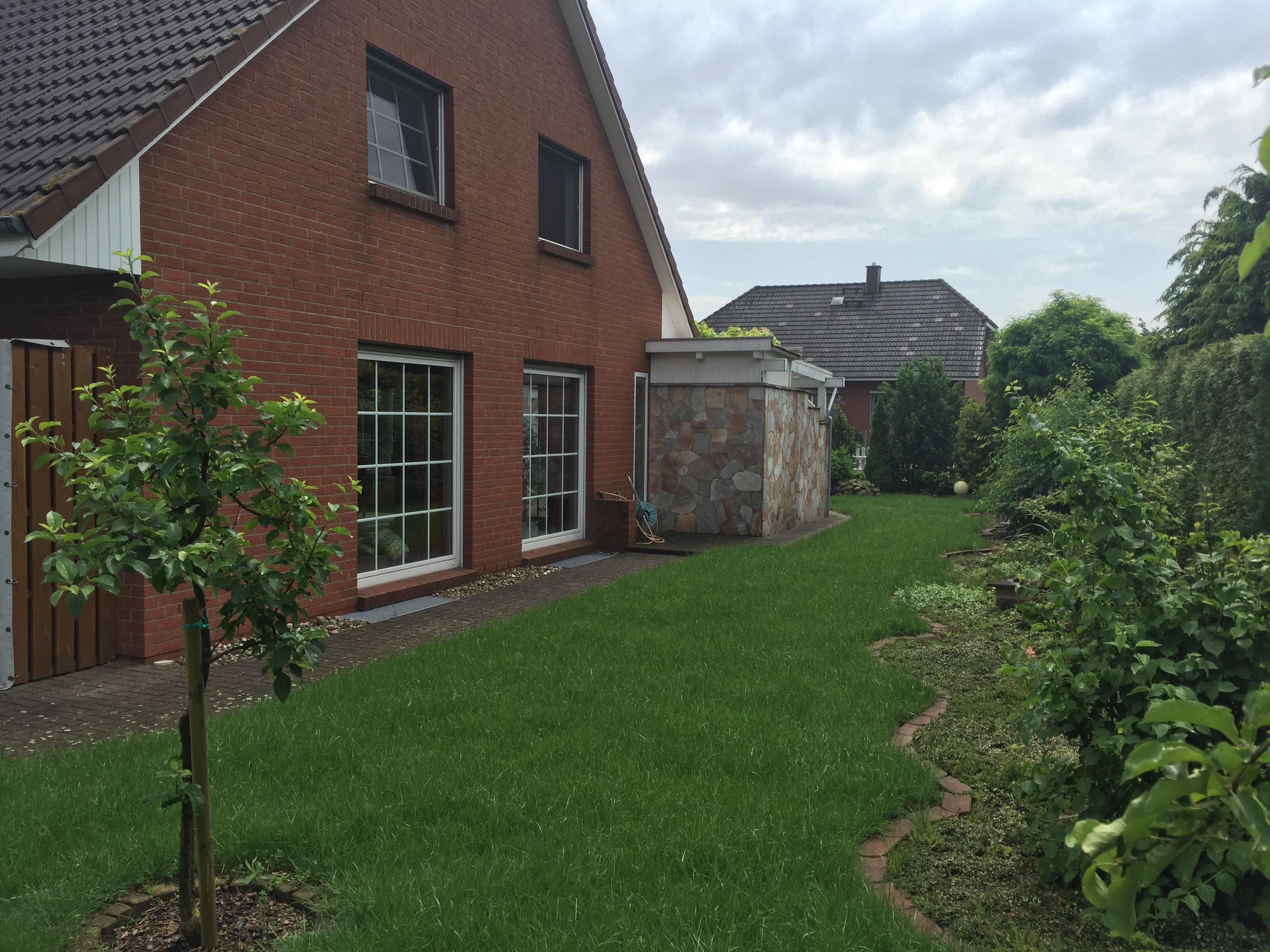 Blick auf den Garten mit großen Wohnzimmerfenstern
